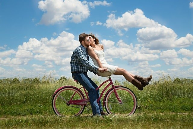 Couple on a bike riding through the fields