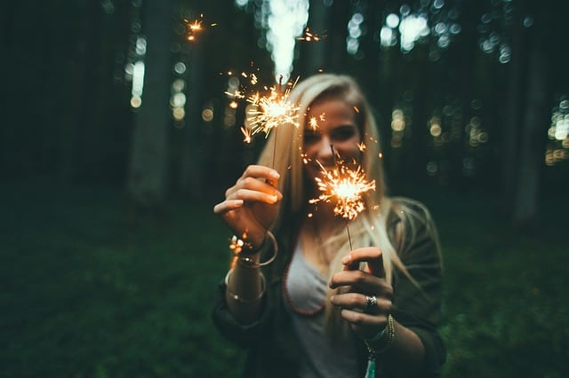 Woman holding up 2 sparklers in the forest